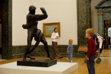 A small child looking at a sculpture in one of the galleries at Tate Britain