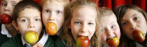 Children with apples in their mouths