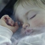 very young child asleep with visible smoke near them
