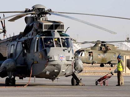 Ground crew carrying out checks on a Sea King ASaC as a RAF Merlin Mk3 taxis at Camp Bastion