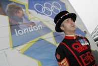 A beefeater standing in front of the London 2012 Olympics logo.
