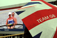 A fan shelters under an umbrella to watch team GB Rowers go for Gold on giant screens in the Olympic Park, in Stratford east London.