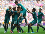 Oribe Peralta of Mexico is mobbed by team-mates after scoring the second goal