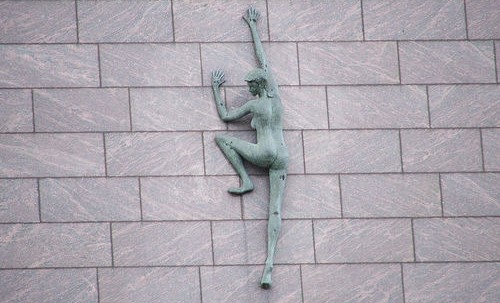 statue climbing a wall representing aspiration