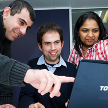 People involved in a coaching session working together at the computer