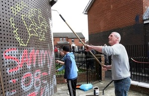 Volunteers cleaning graffiti off walls