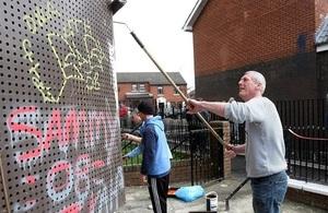 Volunteers cleaning graffiti off walls