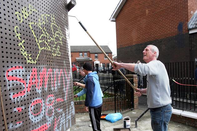 Men removing graffiti