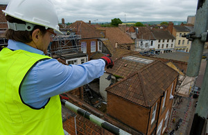 Man in a hardhat surveying a building