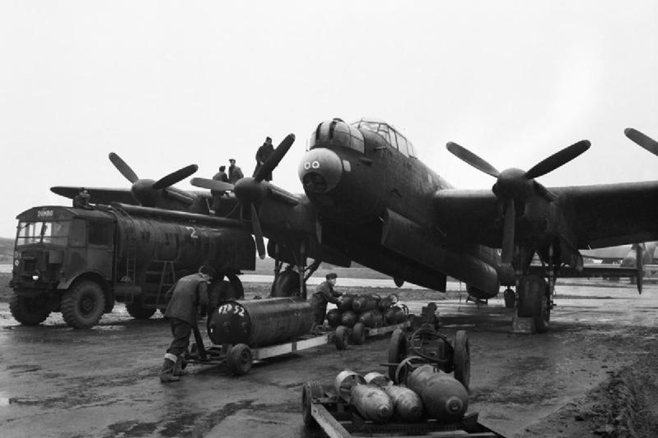 Ground crews refuelling and bombing up an Avro Lancaster of No 75 (New Zealand) Squadron