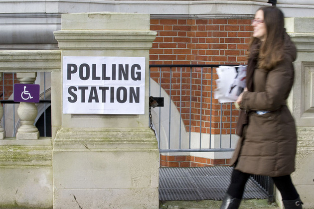 Woman walking past voting sign