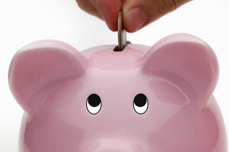 Money being inserted into a piggy bank