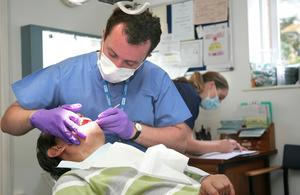 NHS dentist treating man