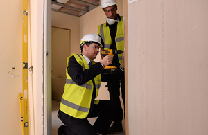 Chancellor drilling a hinge on a door