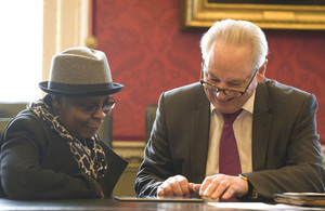 Francis Maude helping a woman use a digital device at the Digital Friends launch.