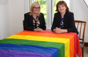 Image of Nicky Morgan MP and Caroline Dinenage MP with a rainbow flag.