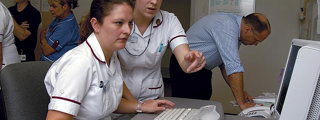 Nurses pointing at computer
