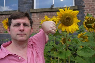 Jonathan with thumbs down next to a sunflower head that is still in bloom and not ready for counting
