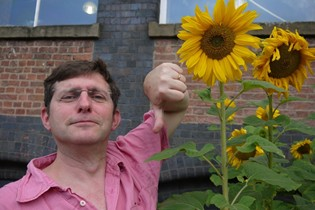 Jonathan with thumbs down next to a sunflower head with petals that is not yet ready for counting