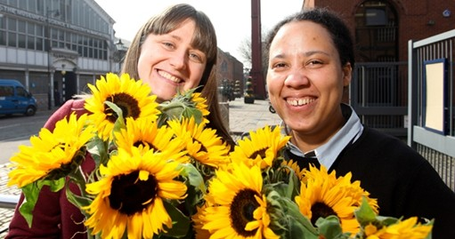 Natalie Ireland and Erinma Ochu clutching bunches of sunflowers