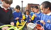 Schoolchildren water their freshly planted seeds