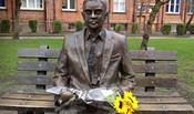 Statue of Alan Turing in Sackville Gardens, Manchester, with a bunch of sunflowers