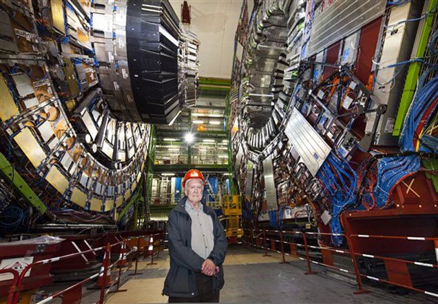 Peter Higgs stands in front of a huge machine which fills a large chamber.