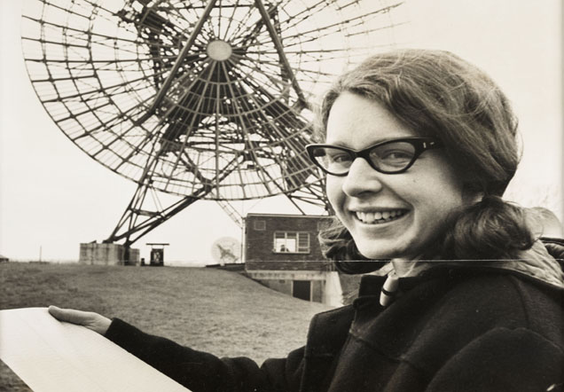 A young woman (Bell) in front of a large circular receiving dish.