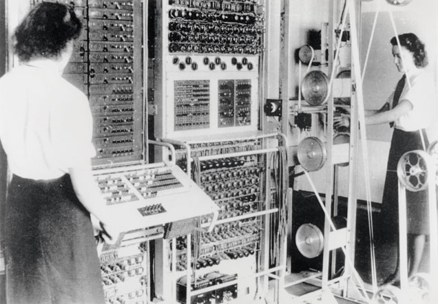 Black-and-white photograph showing two women standing next to a bank of computer equipment.