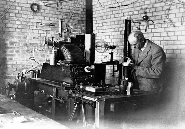 Francis William Aston examines apparatus resting on a work bench. Other laboratory apparatus can be seen on the wall behind him.