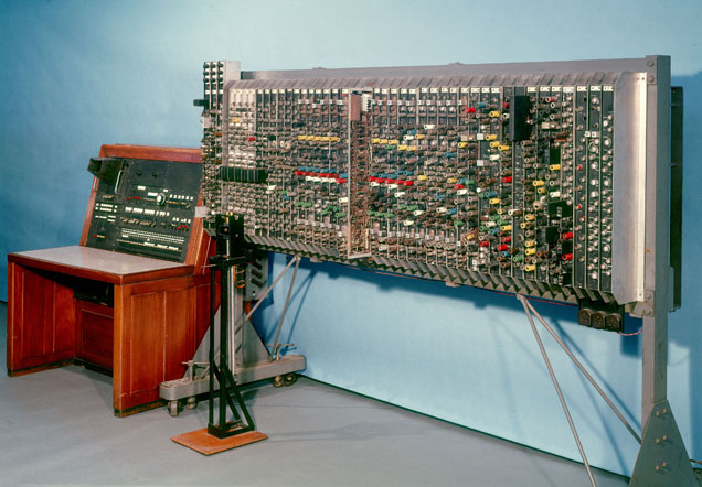 A large object made up of a wooden computer desk and a freestanding panel. The desk has dials and switches on it. The panel has hundreds of glass valves, some with coloured sleeves.