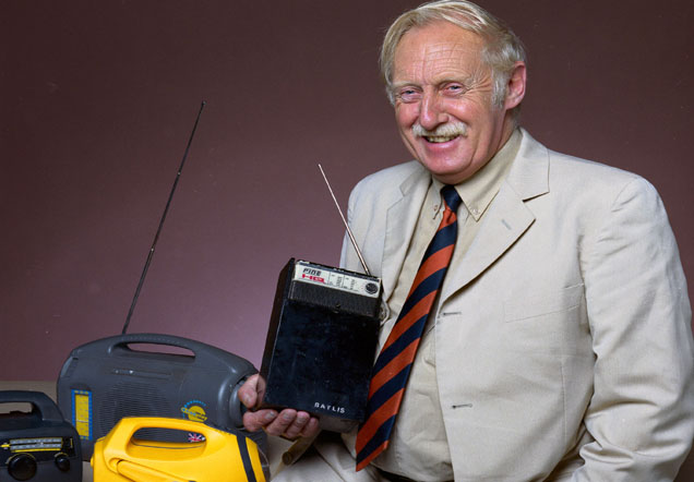Trevor Baylis holding a rectangular, black radio. Other radios are in the background.