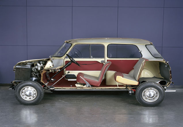 Side view of a Mini car with doors and side removed, exposing the insides.