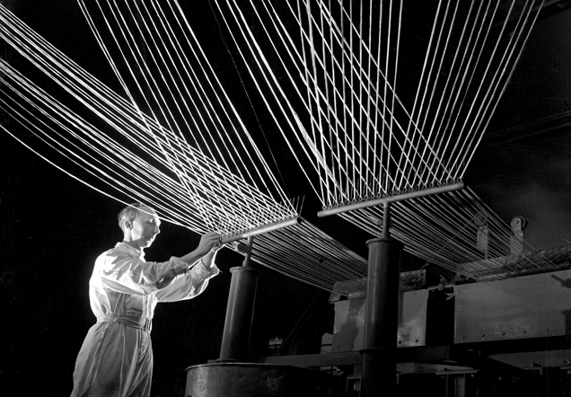 A man in a white coat adjusts an industrial-sized loom. Fibres stretch out of it in all directions.