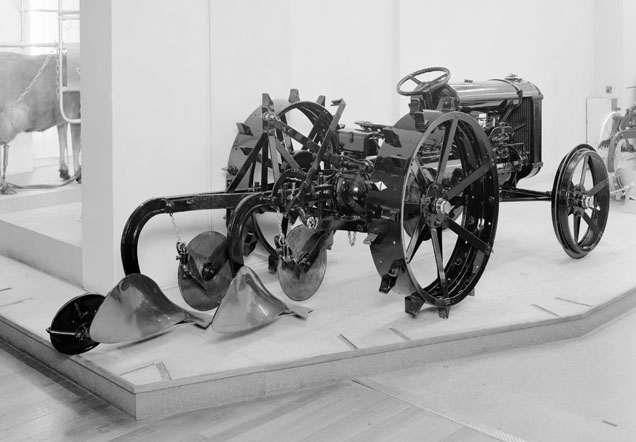 Black-and-white photograph of a tractor on display in the Museum, with a plough mounted on the tractor's back and attached directly to it.
