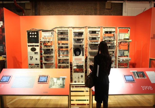 A woman standing in front of a museum display of racks of computer equipment.