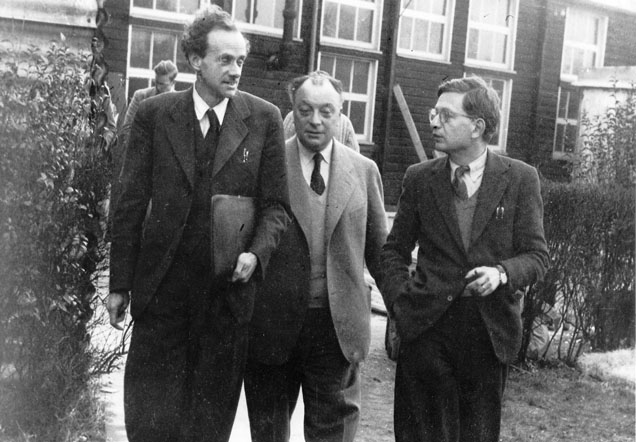 Black and white image of the three physicists walking up a path.