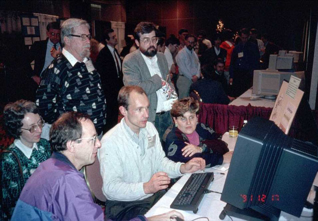 People gathered around a computer demonstration by Tim Berners-Lee.