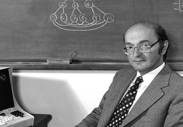 Donald Davies sits in front of a blackboard while holding a book. A computer is just visible at the left edge of the image.
