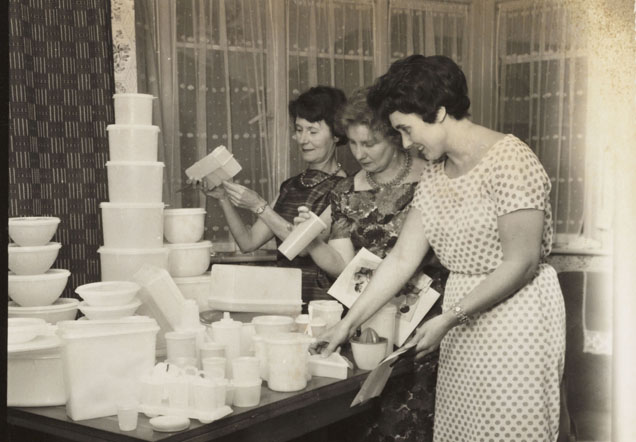 Three women stand by a table admiring a pile of Tupperware.