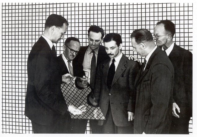 Black-and-white photograph of six men in suits inspecting a piece of glass.
