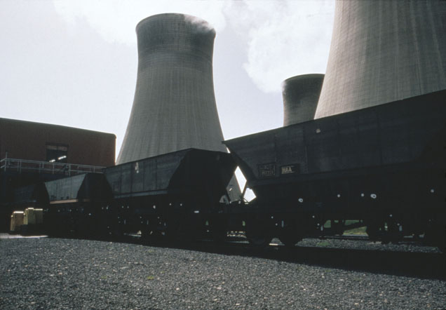 Railway freight wagons moving along track are in the foreground. In the background are the large cooling towers of a power station.