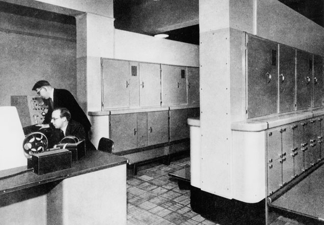 Black-and-white photograph showing a large room full of computer banks. Two men on the left of the image are at a desk.