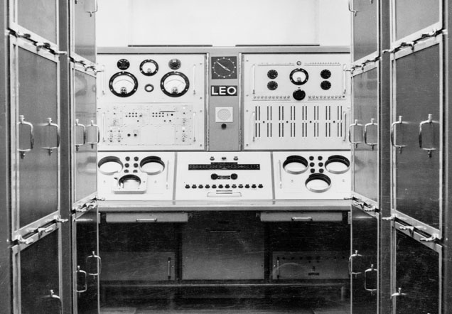 View of a computer terminal that fills a whole room. On the terminal are buttons and dials and a plaque reading 'LEO'.