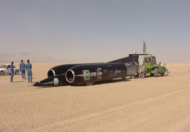 Vehicle with large engines on either side in the desert.