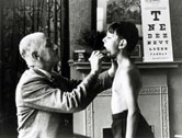 image: A doctor checks a young boy's tonsils, December 1935