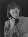 Woman answering a telephone, about 1950